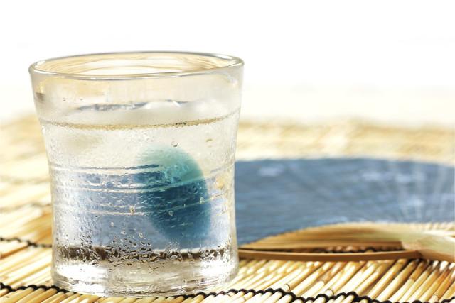 冷たい日本酒の入ったグラスとうちわ