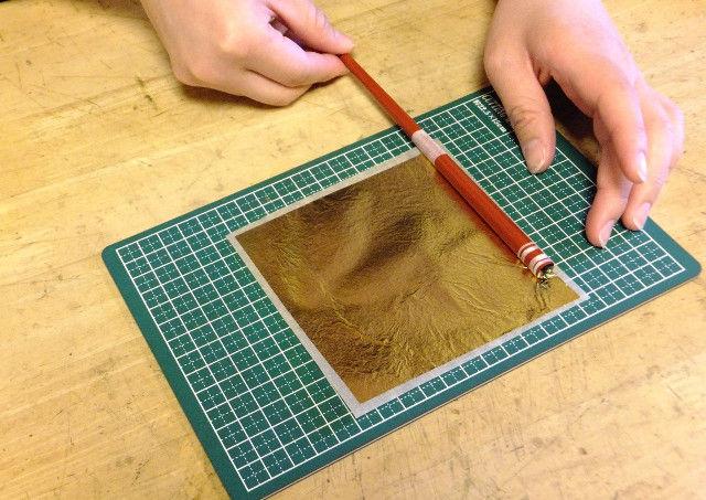 箸に金箔を貼り付ける作業をする手